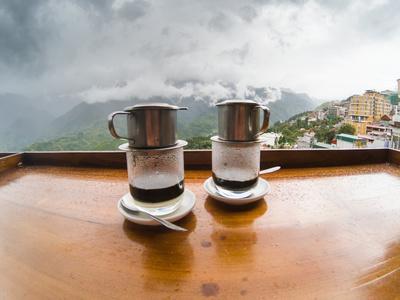 enjoying hot vietnamese black coffee on a restaurant terrace in Sapa