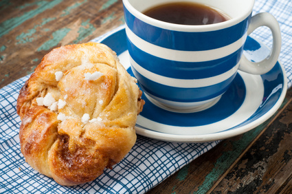 Swedish cinnamon berry bun served on a rustic wooden table with a cup of freshly brewed coffee in a blue and white striped cup and saucer. Coffee and a bun is a tradition in Sweden known as fika.