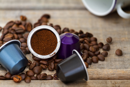 Italian espresso coffee capsules or coffee pods on wood background with some roasted coffee beans