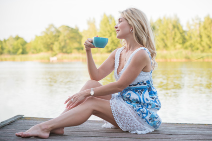 Nice blonde woman on a lake, concept of tranquil and rest. Nature landscape